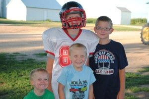 Scooter and his older/younger brothers. He's the one in the football gear.