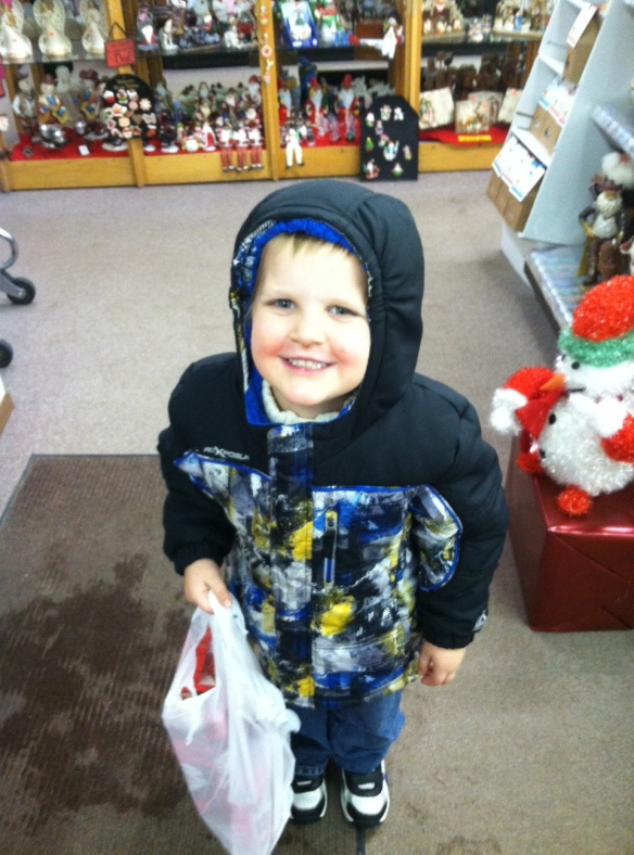 A happy boy, with his gift for his brother all wrapped and ready for the tree!